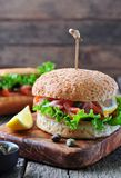 Burger with pickled salmon, lettuce, white onion and capers Stock Image