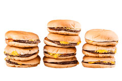 Burger piles. A very tall pile of cheesburgers isolated over a white background stock photography