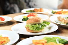 Burger and a plate of delicious dishes on the table in the resta Royalty Free Stock Photos