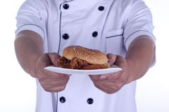 Burger on plate in hands of chef Stock Image