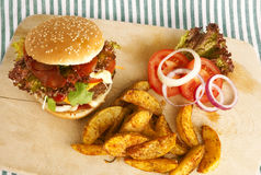 Burger with potato wedges on board. Green and white striped tablecloth, tomatoes as decoration Stock Images