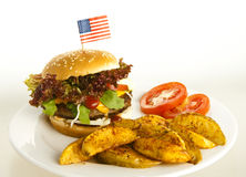 Burger with potato wedges. On plate; background white , tomatoes as decoration Stock Photo