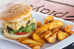 Burger. With potato wedges on a square plate Royalty Free Stock Image