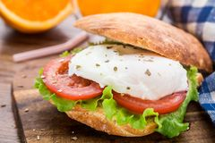 Burger with pouched egg and tomato Stock Image