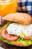 Burger with pouched egg and tomato. For breakfsat Stock Photos
