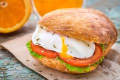 Burger with pouched egg and tomato. For breakfsat Royalty Free Stock Images
