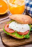 Burger with pouched egg and tomato. For breakfsat Royalty Free Stock Image