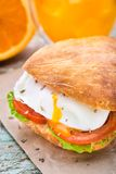 Burger with pouched egg and tomato. For breakfsat Royalty Free Stock Photography