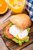 Burger with pouched egg and tomato. For breakfsat Stock Photography