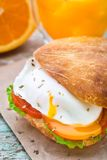Burger with pouched egg and tomato. For breakfsat Royalty Free Stock Photo