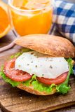 Burger with pouched egg and tomato. For breakfsat Stock Images