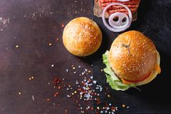 Burger and raw cutlet. Fresh homemade burger on black slate and raw cutlet and sliced onion, served with sea salt and pepper over dark background. Top view. With Stock Photo