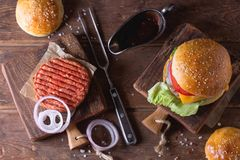 Burger and raw cutlet Stock Images