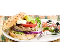Burger and salad. Turkey burger on an onion roll garnished with red onion, lettuce, egg avocado,and tomato slices served with a side of greek salad and a Stock Image