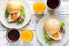 Burger sandwich, cup of tea and orange juice for breakfast Royalty Free Stock Photos