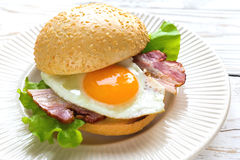 Burger sandwich with fried egg, bacon and salad Stock Images