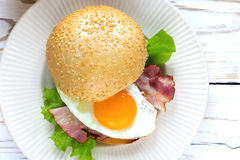 Burger sandwich with fried egg, bacon and salad Royalty Free Stock Images