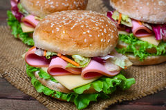 Burger sandwich with sausage, cheese and vegetables on a wooden background Stock Images