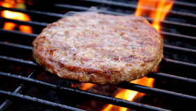 Burger Sizzling On The Grill Stock Photo