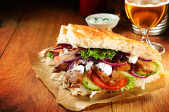 Burger Slice with Grilled Meat Doner and Veggies. Close up Burger Slice with Grilled Meat Doner and Veggies on Brown Paper, Placed on Wooden Table royalty free stock image