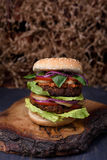 Burger with succulent beef patty and fresh vegetable ingredients served on a rough wood board. Royalty Free Stock Image