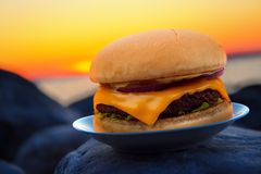 Burger and sunset. Cheese burger on beach rock in evening sunset Stock Images