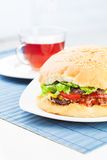 Burger on a table. Burger and cup of tea on a table Royalty Free Stock Photo
