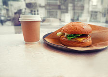 Burger and takeaway coffe  on table in pub selective focus, toned shot Royalty Free Stock Photo