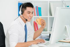Burger telecom. Telecom worker eating a sandwich while consulting clients online Royalty Free Stock Photo