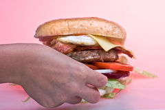 Burger Time. Australian Hamburger being grabbed by hand Stock Photos