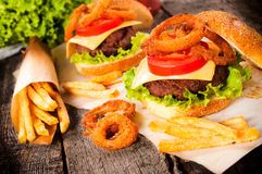Burger time. Big and tasty beef burger with onion rings and french fries.Selective focus on the burger Royalty Free Stock Photos