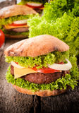 Burger time. Cheeseburger with vegetables on the wooden table Stock Photos