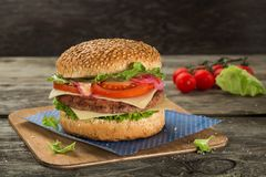 Tasty and appetising cheeseburger with tomato and green salad served on the wooden table. Burger with tomato and green salad served on the wooden table royalty free stock image
