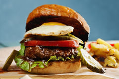 Burger topped with sunny egg closeup Royalty Free Stock Photo