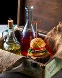 Burger und Flaschen Öl und Soße auf dem Hintergrund eines Dekors Stockbild
