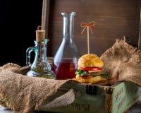 Burger und Flaschen Öl und Soße auf dem Hintergrund eines Dekors Stockfotografie
