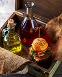 Burger und Flaschen Öl und Soße auf dem Hintergrund eines Dekors Lizenzfreies Stockfoto