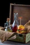 Burger und Flaschen Öl und Soße auf dem Hintergrund eines Dekors Lizenzfreie Stockfotografie