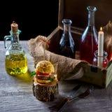 Burger und Flaschen Öl und Soße auf dem Hintergrund eines Dekors Stockfotos
