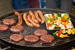 Burger und Würste auf Grill Stockfotos