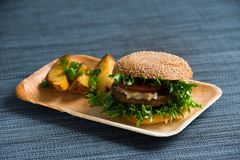 Burger Vegan με τις ψημένες πατάτες, γαλαζωπό υπόβαθρο στοκ φωτογραφία με δικαίωμα ελεύθερης χρήσης