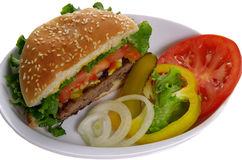 Burger with vegetables. Beef burger with sliced vegetables on side, served on white plate stock photo