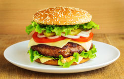 Burger in a white plate. On wooden table Stock Photography