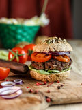 Burger and Whole Wheat Bread. Home made burger with beef, vegetables and whole wheat bread royalty free stock image