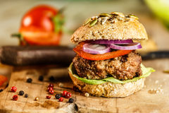 Burger and Whole Wheat Bread. Home made burger with beef, vegetables and whole wheat bread stock photo