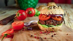 Burger and Whole Wheat Bread. Home made burger with beef, vegetables and whole wheat bread stock photography