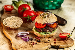 Burger and Whole Wheat Bread. Home made burger with beef, vegetables and whole wheat bread stock photos