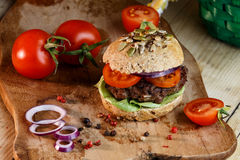 Burger and Whole Wheat Bread. Home made burger with beef, vegetables and whole wheat bread royalty free stock images
