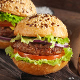 Burger on wooden background closeup. With copy space. Selective focus. square frame royalty free stock image