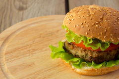 Burger on wooden plate right Royalty Free Stock Photos